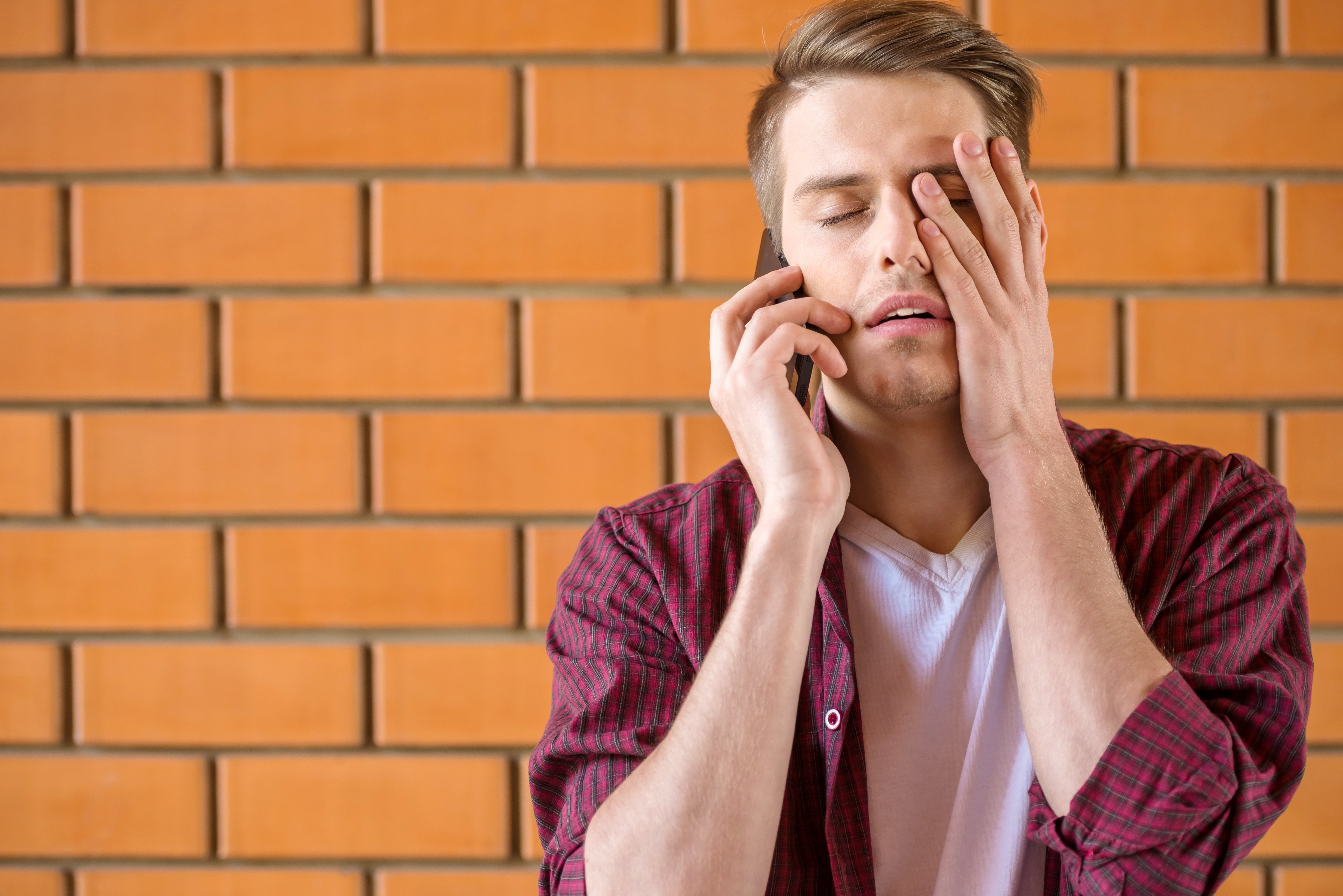 Frustrated man talking on a cellphone. | Source: Shutterstock