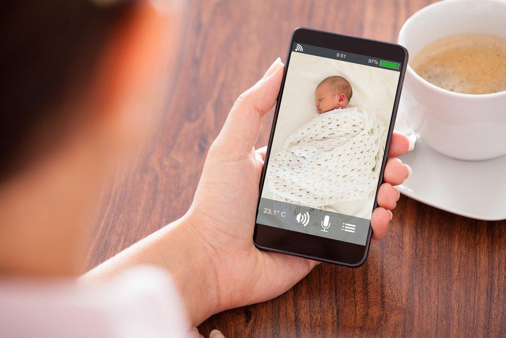 Une mère surveille son bébé via Video Babyphone.   Shutterstock