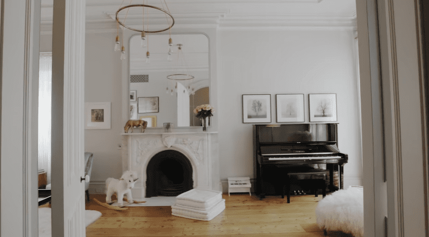 The parlor floor has a family room with a piano and fireplace | Source: YouTube/Architectural Digest