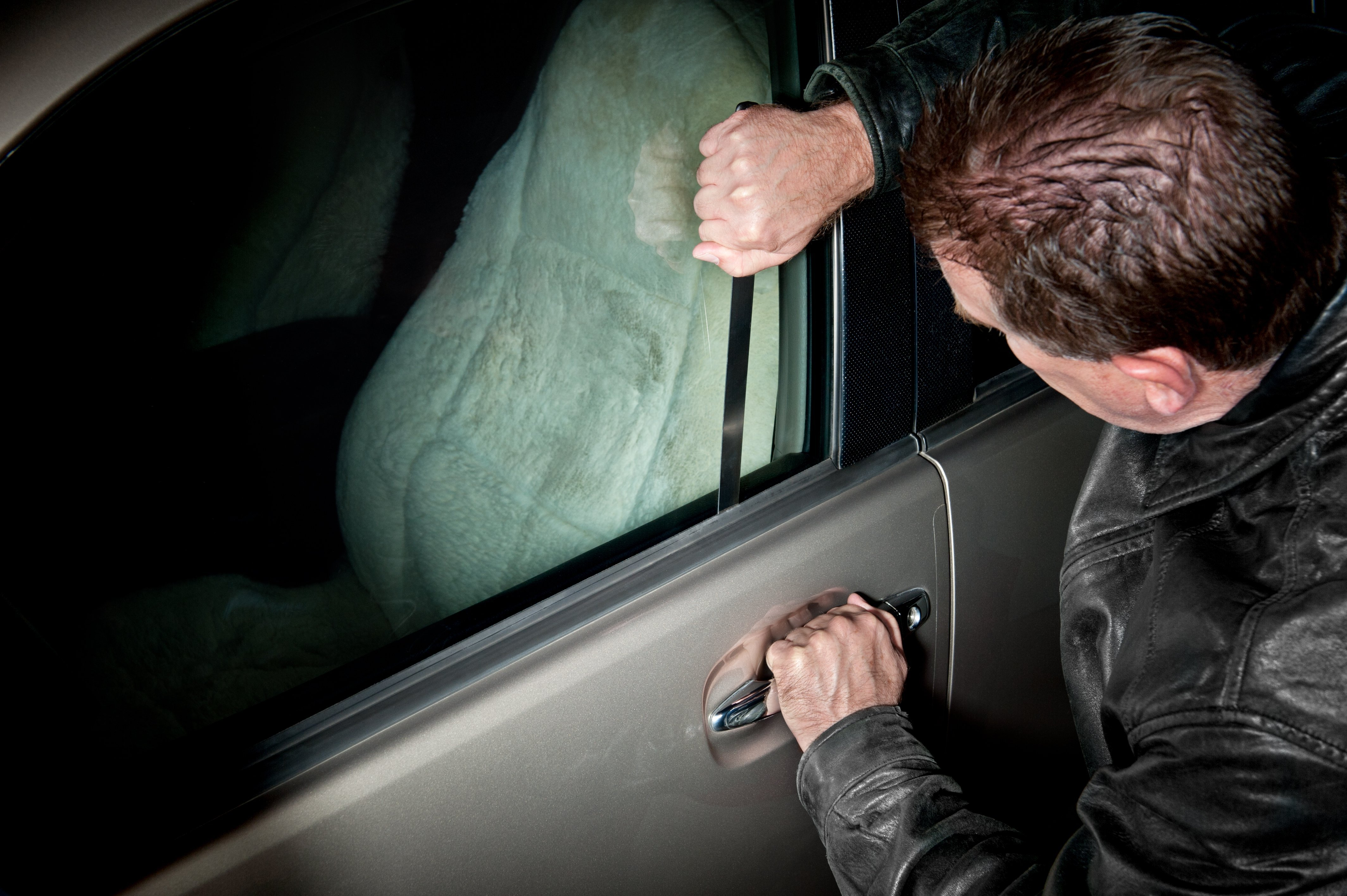A man trying to open a car door at night. | Source: Shutterstock.