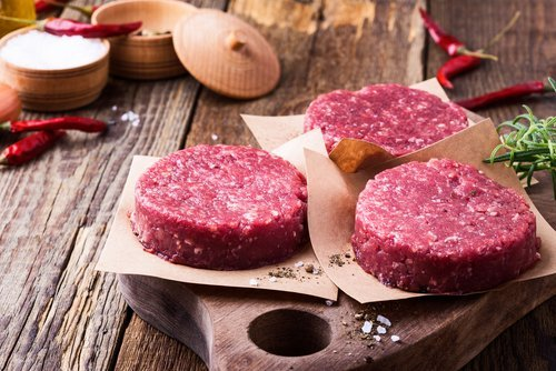 Organic raw ground beef, round patties for making homemade burger on wooden cutting board. | Source: Shutterstock