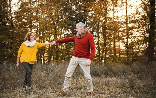 Photo of a senior couple on a walk in an autumn nature at sunset, holding hands. | Photo: Getty Images