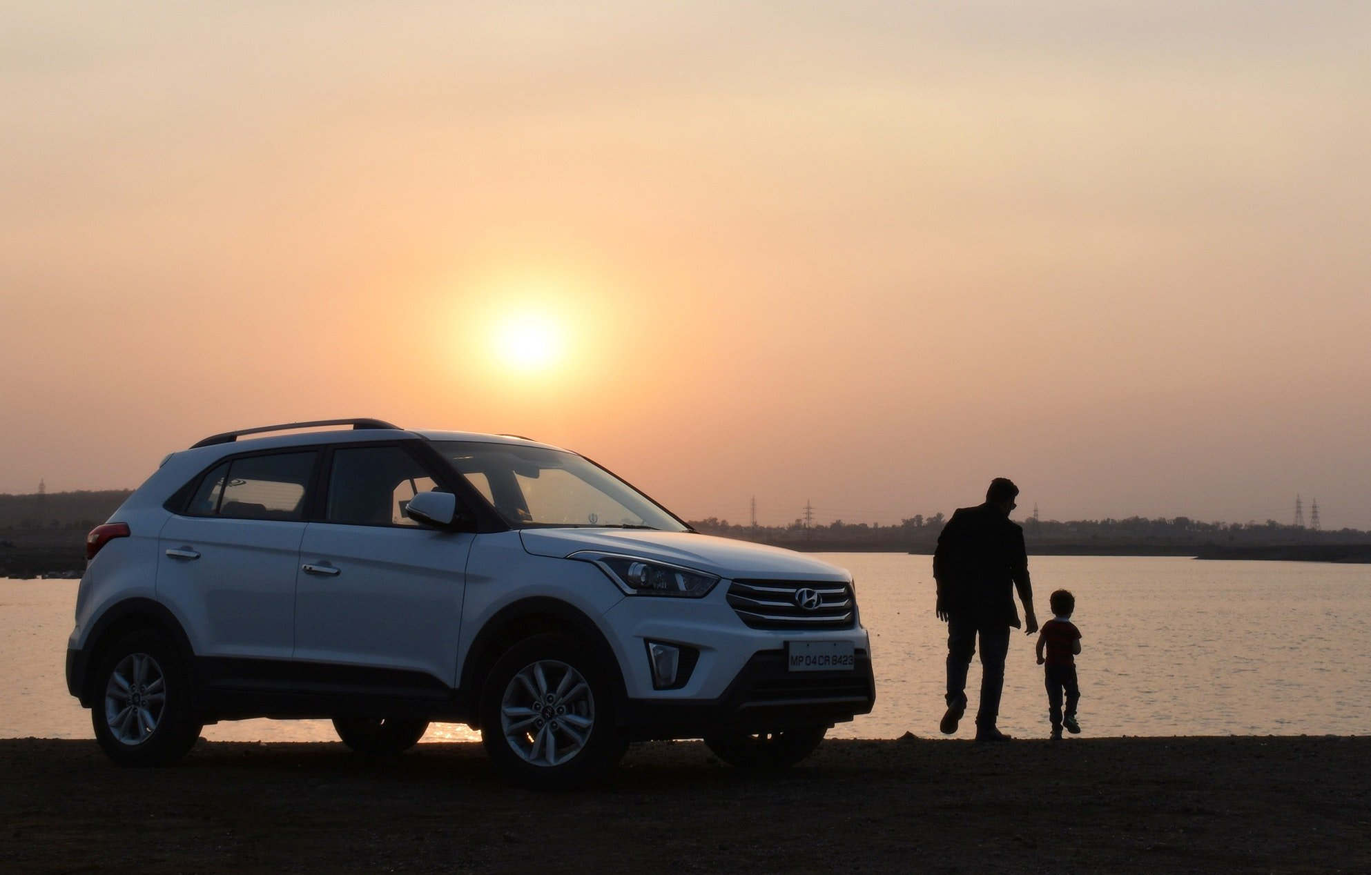 Pictured - A silhouette of a man and child near a white Hyundai Tucson SUV during the sunset | Source: Pexels