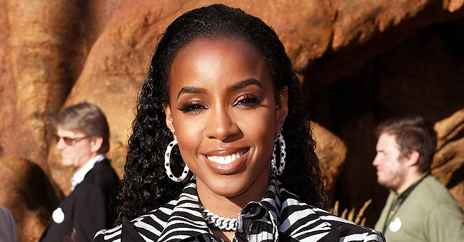 Kelly Rowland Flaunts Ample Cleavage & Curves in Purple Tassel Jumpsuit in Stunning Photoshoot