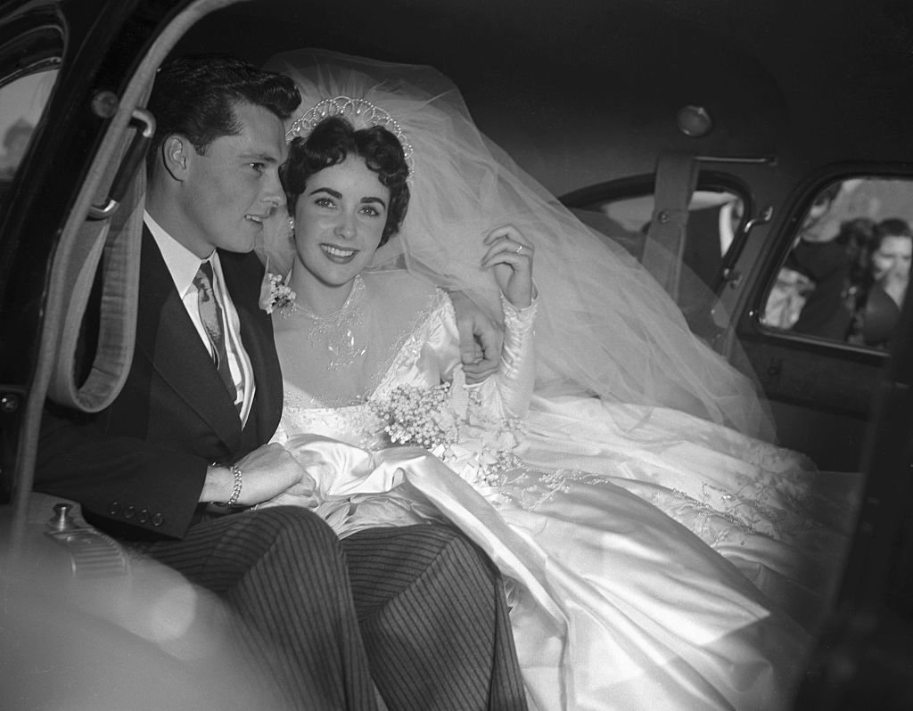 """Elizabeth Taylor and her groom, Conrad """"Nickie"""" Hilton, Jr. in the limousine that will take them to their wedding reception at the Bel-Air Country Club. 