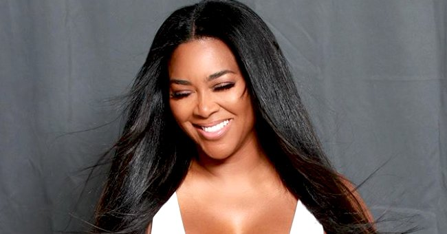 Kenya Moore's Daughter Brooklyn Poses in a Swimsuit & Hat While Winking at the Camera (Photo)