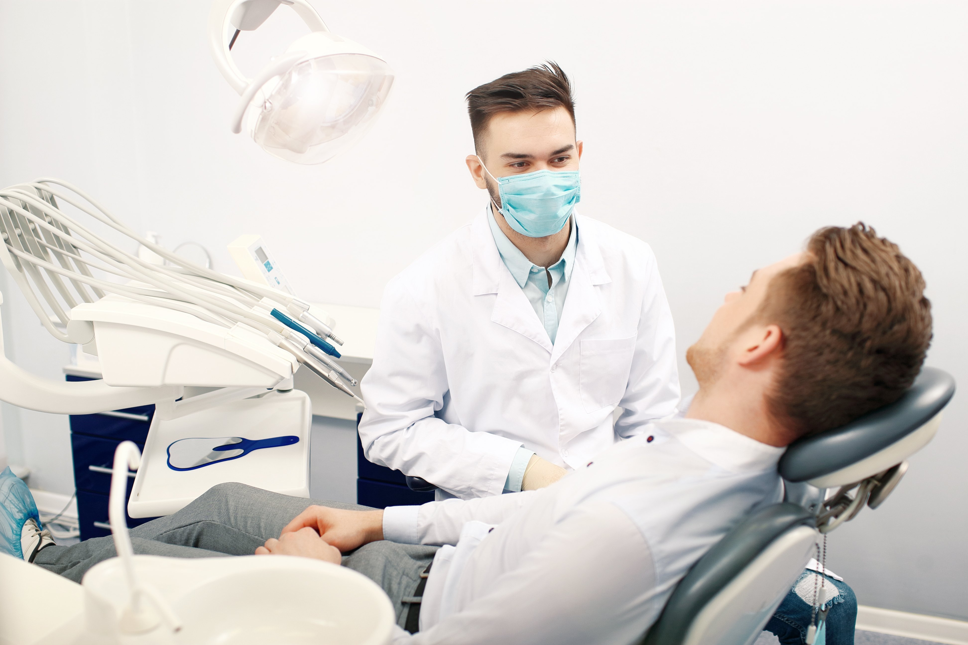 A young male dentist and a patient | Photo: Shutterstock.com