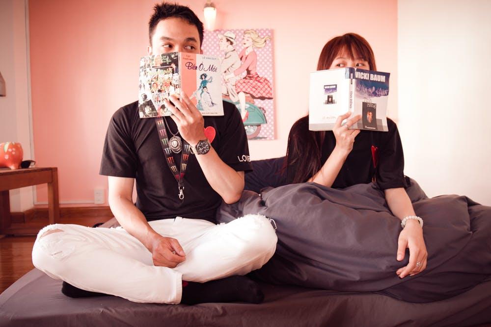 Un couple assis sur un lit et tenant des livres. | Photo : Pexels