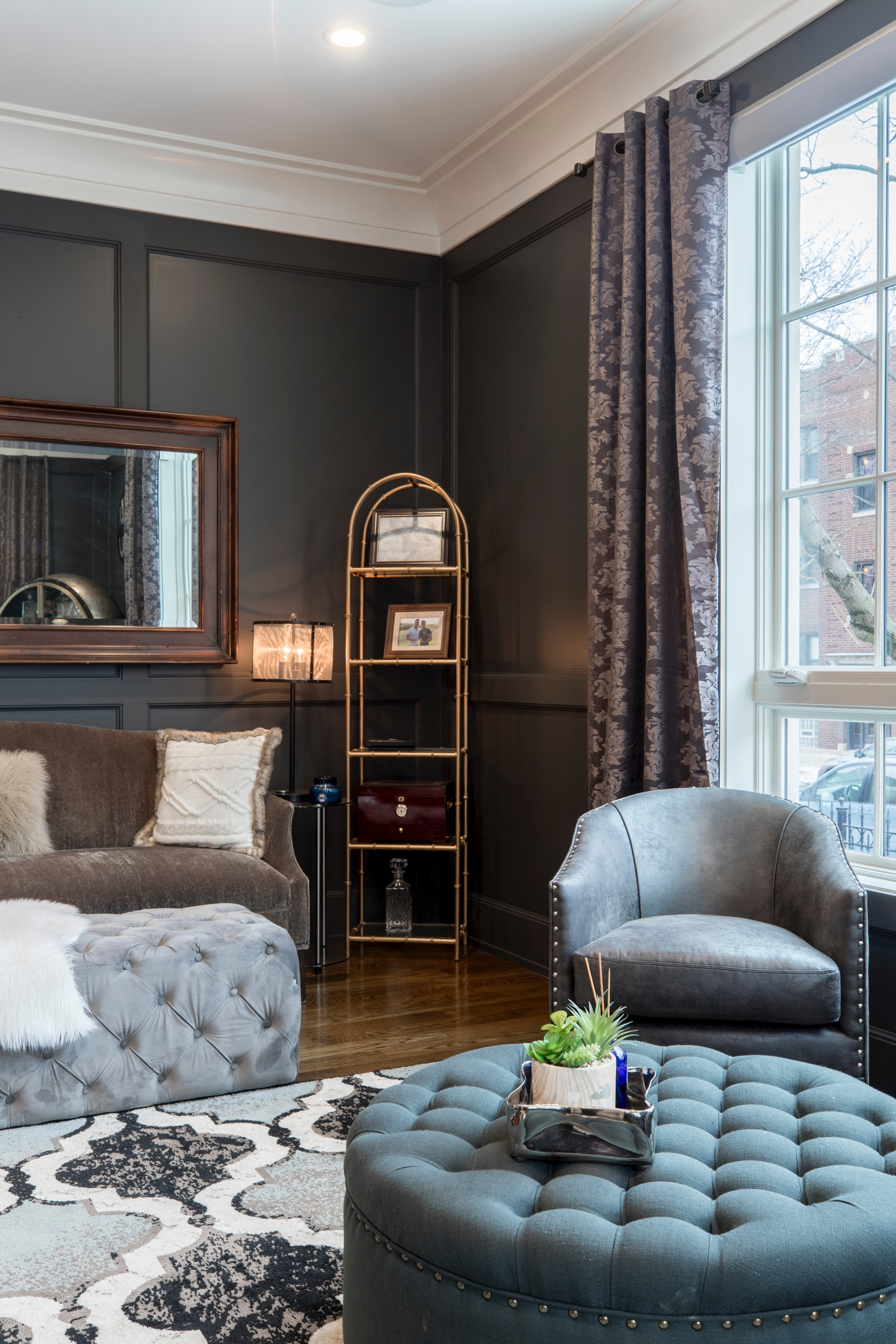 Pictured - An interior design of a house, a gray leather tub chair, a blue ottoman and dark gray walls   Source: Pexels