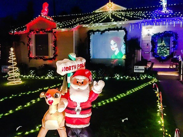 Santa and Rudolph the red nosed reindeer and a video screen projection are part of a private homes Christmas lights display on candy cane lane in El Segundo | Photo: Getty Images