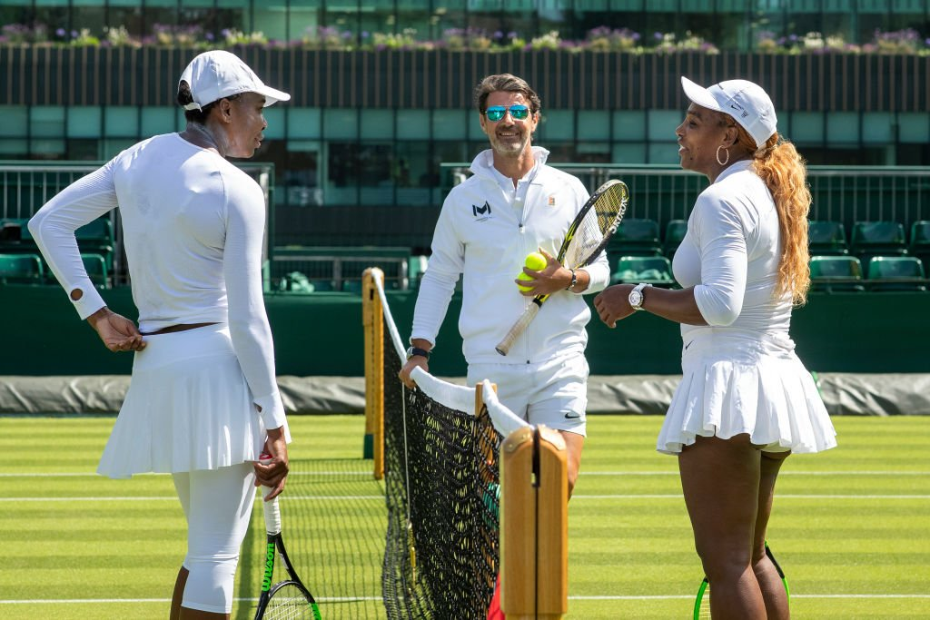 Serena Williams with sister Venus Williams of the United States and coach Patrick Mouratoglou at training before the start of the Wimbledon Lawn Tennis Championships | Photo: Getty Images