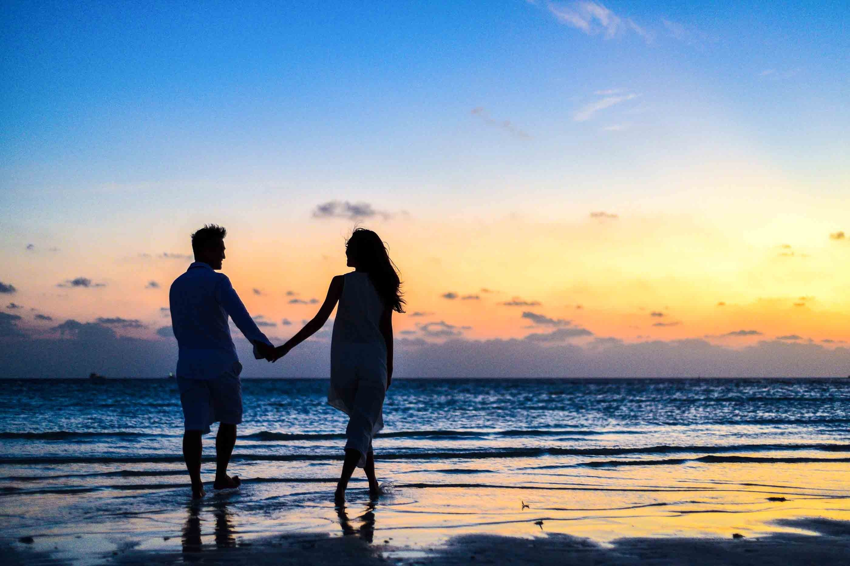 A man and a woman holding hands on a seashore during sunrise.   Photo: Pexels