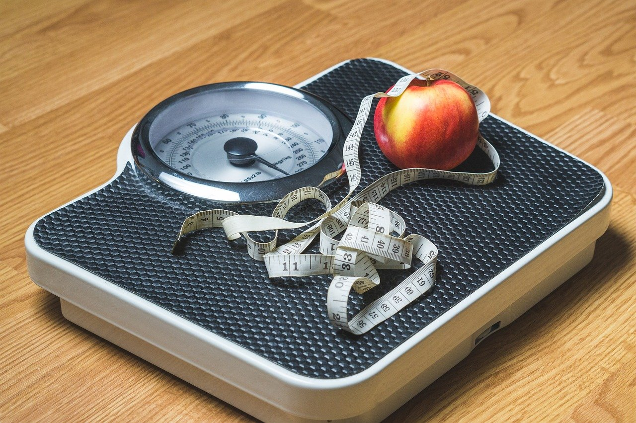 A photo of a scale, measuring tape, and an apple | Photo: Needpix/TeroVesalainen