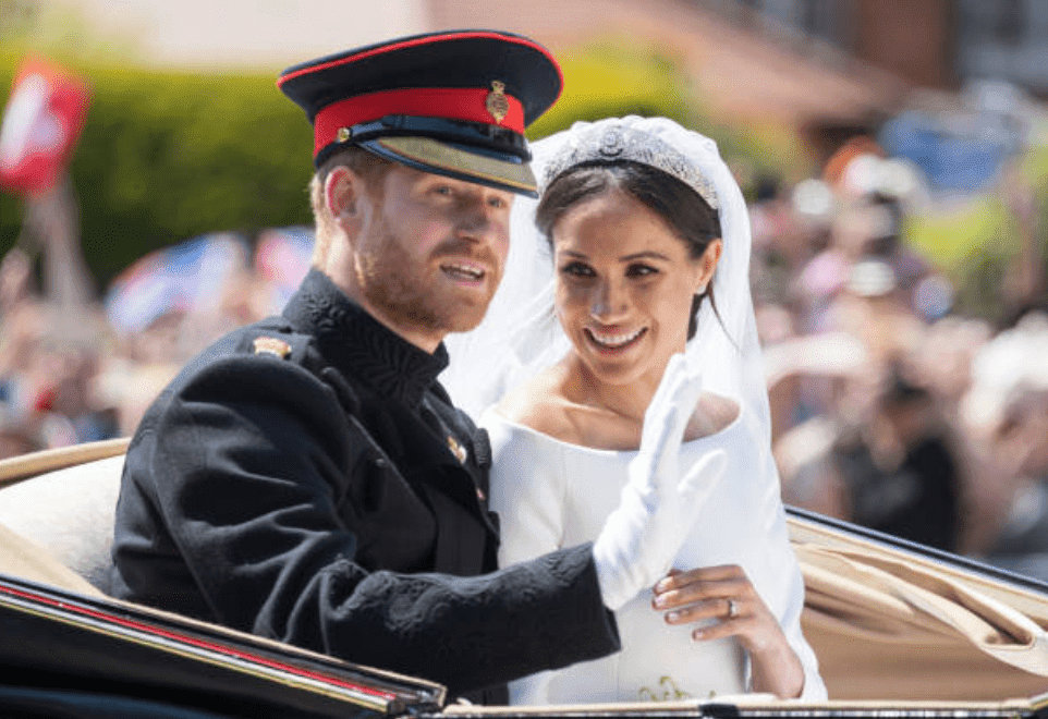 Prince Harry and Meghan Markle wave to the public as they ride by carriage after their wedding at St George's Chapel, Windsor Castle on May 19, 2018, in Windsor, England | Source: Getty Images (Photo by Pool/Samir Hussein/WireImage)