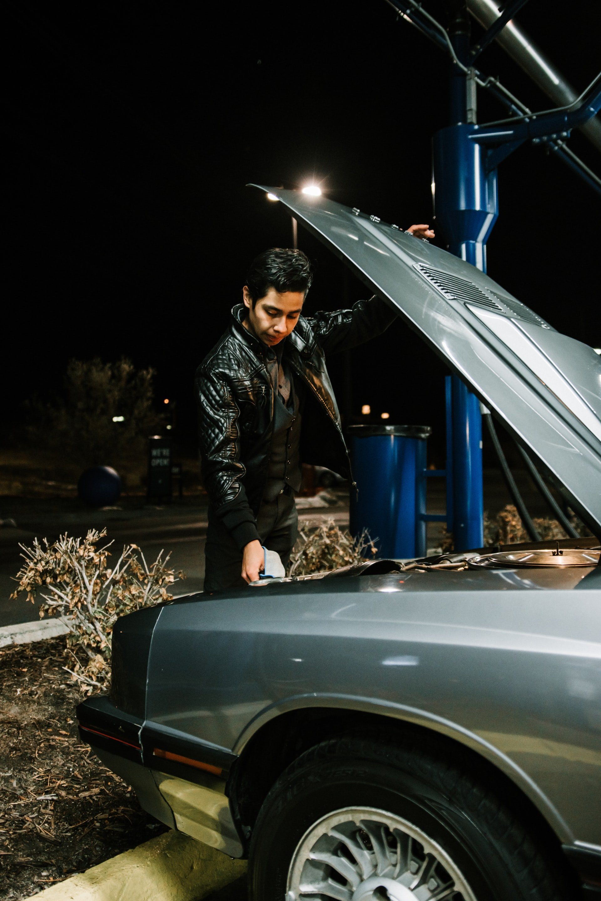A young man holding up a hood of a car   Source: Unsplash