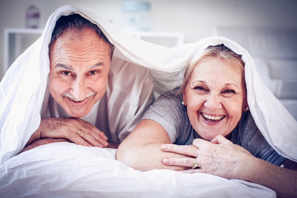 Elderly couple snoozing in bed  | Shutterstock