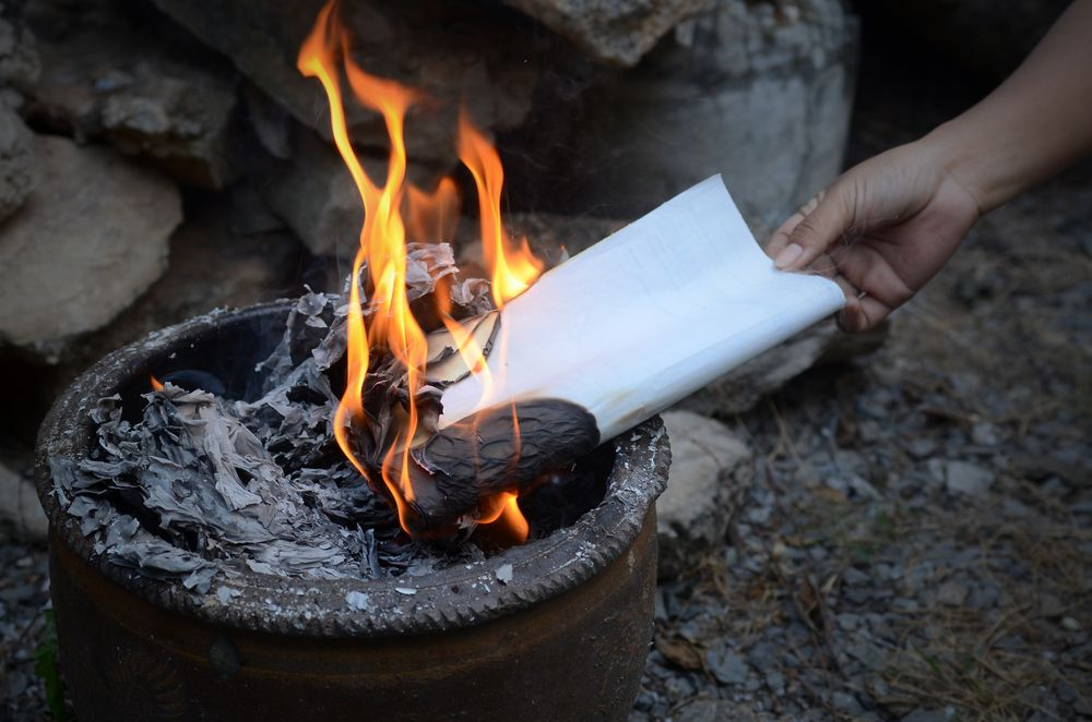 A letter being thrown to the fire. | Source: Shutterstock