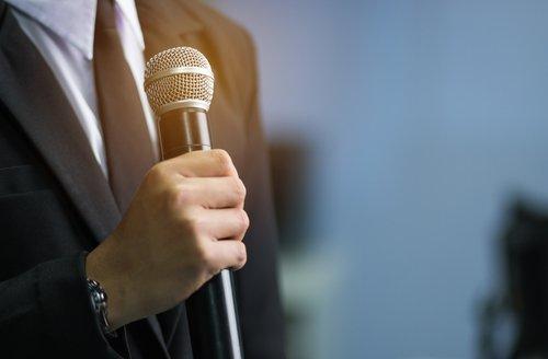 A man talking over a microphone. | Source: Shutterstock.