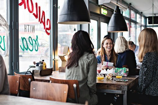 Smiling female friends enjoying while sitting at dining table for brunch in restaurant | Photo: Getty Images