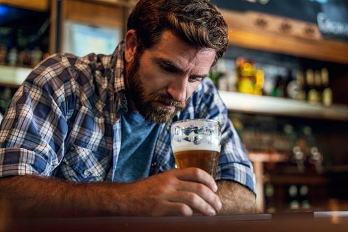 Sad man pictured looking at beer glass while sitting in beer bar | Photo: Getty Images