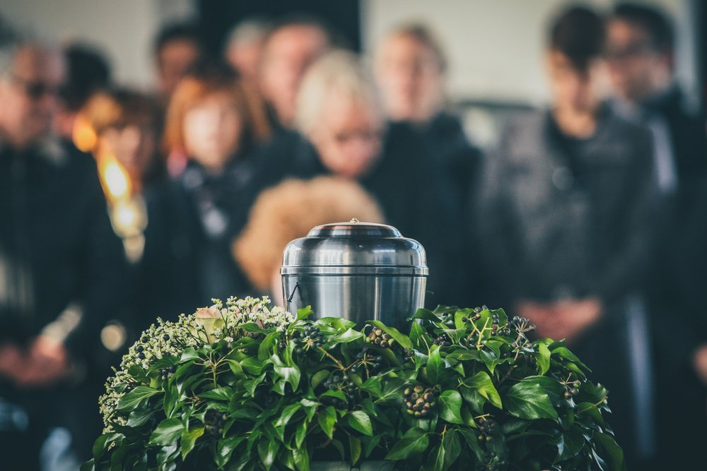 A metal urn with ashes of a dead person on a funeral, with people mourning in the background on a memorial service | Photo: Shutterstock