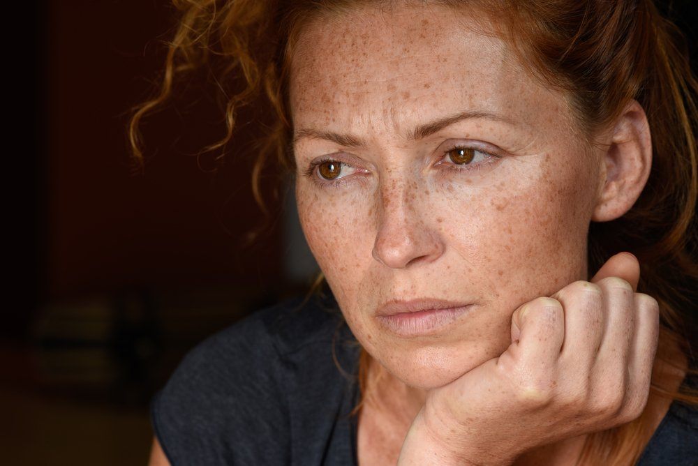 A portrait of a worried red haired woman. | Shutterstock