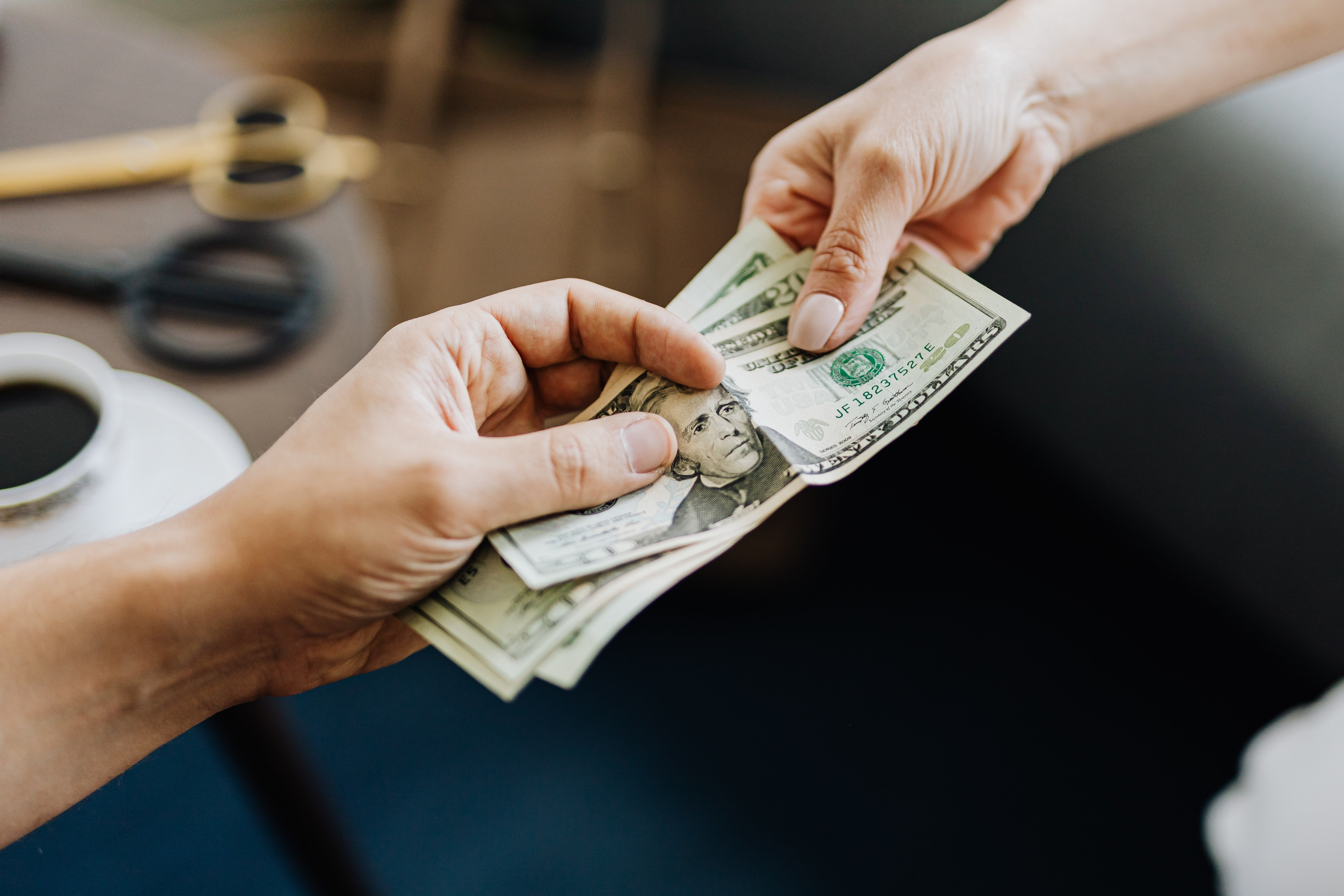 Two hands holding American dollars   Photo: Pexels