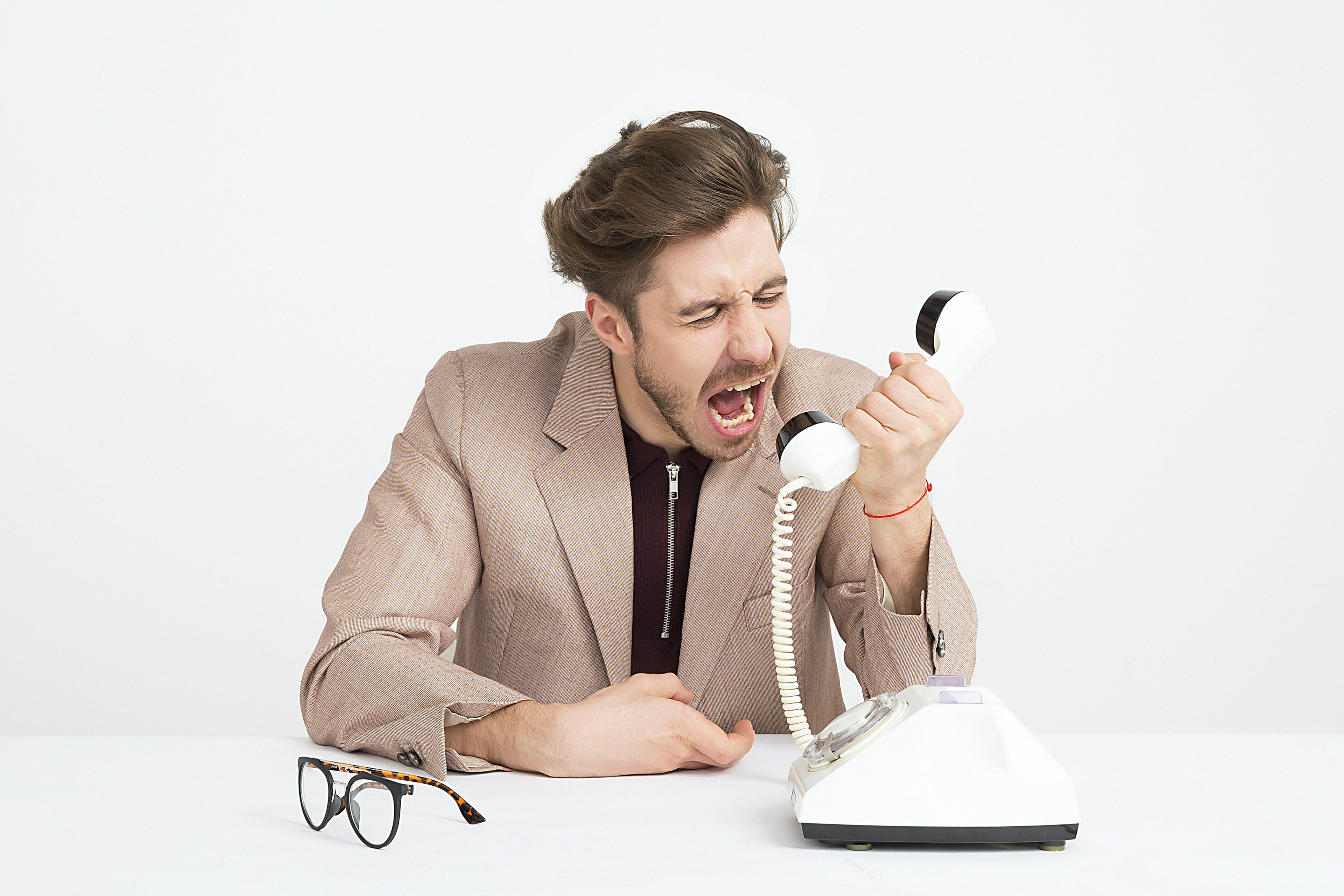 Pictured - A man wearing brown jacket mocking someone on the other end on the telephone | Source: Pexels