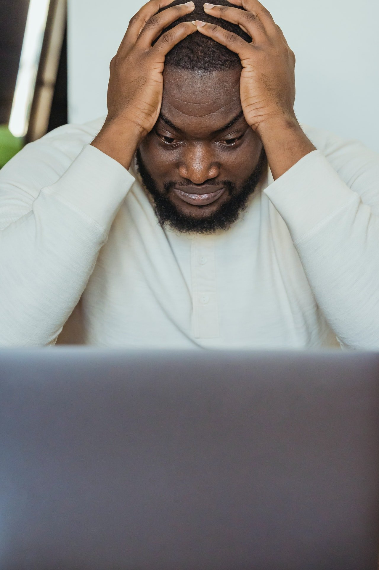 A frustrated man holding his head with both hands. | Source: Pexels