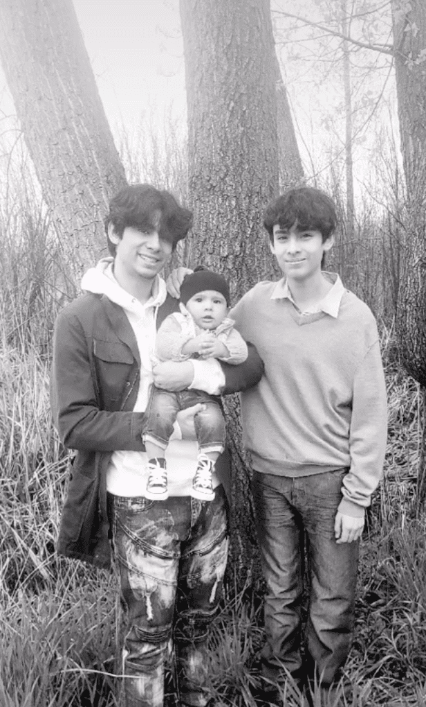 Two brothers smile and stand together as the eldest one proudly holds their newborn sibling | Photo: TikTok/fivedotmom