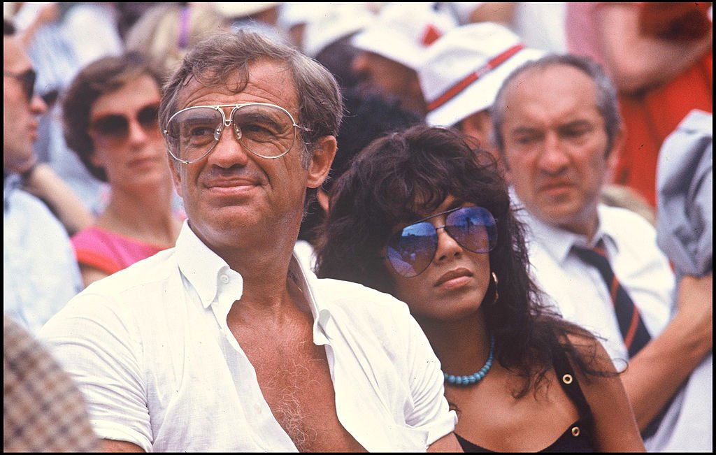 Jean-Paul Belmondo et sa petite amie Carlos Sotto Mayor à Roland Garros, 1982. | Photo : Getty Images