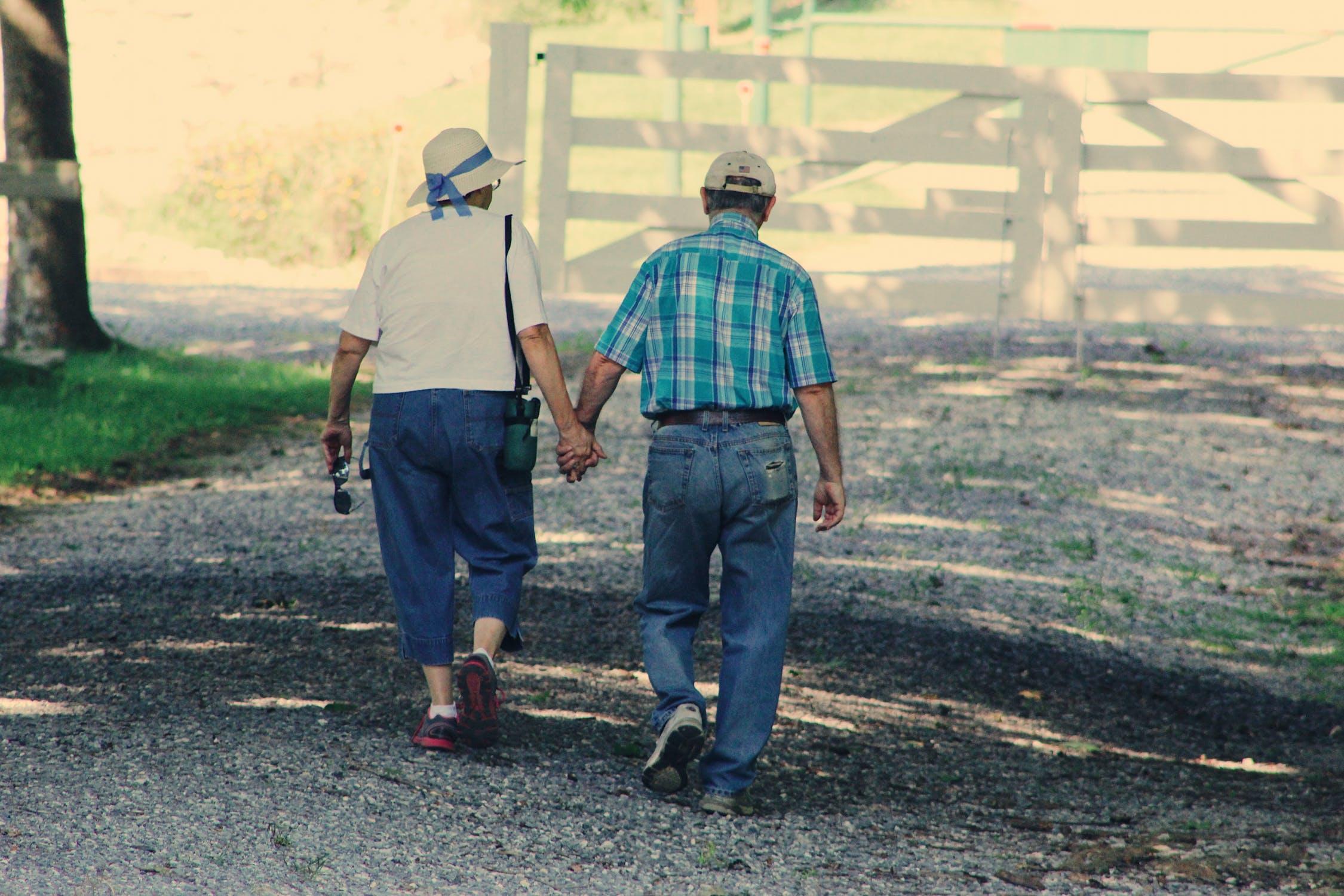 Pareja de ancianos paseando por un camino. | Imagen: Pexels
