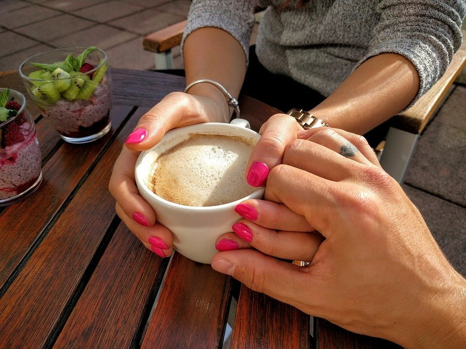 Hands coming together during a coffee date. | Source: Pixabay