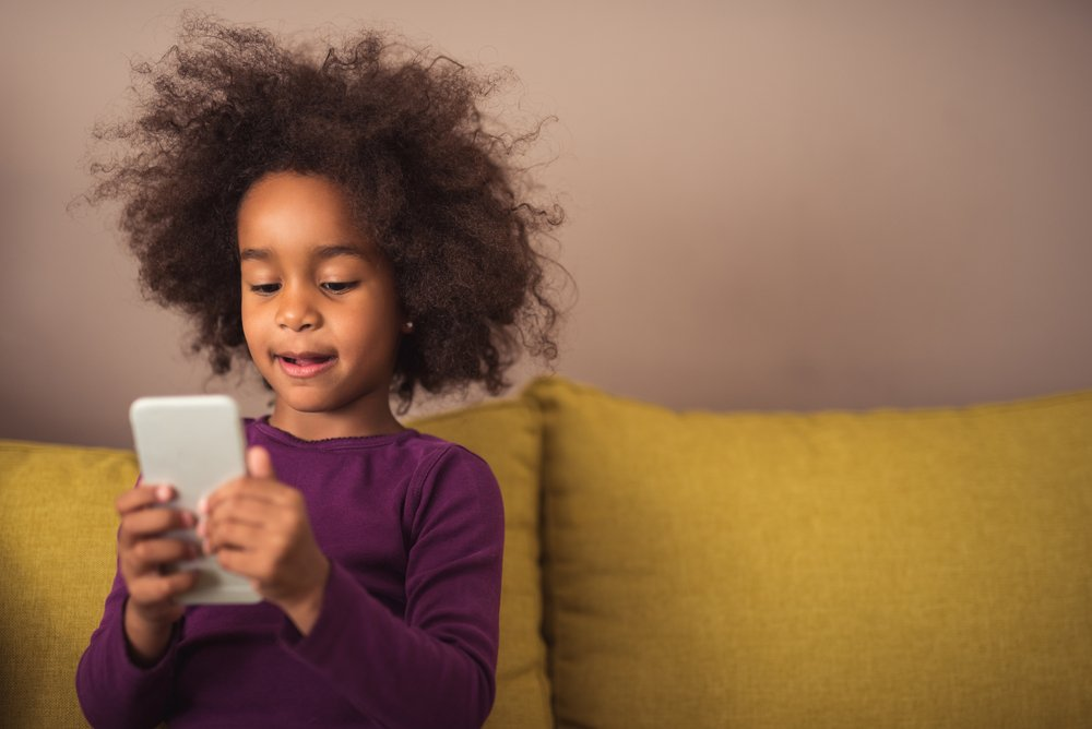 Little girl using cellphone. | Photo: Shutterstock