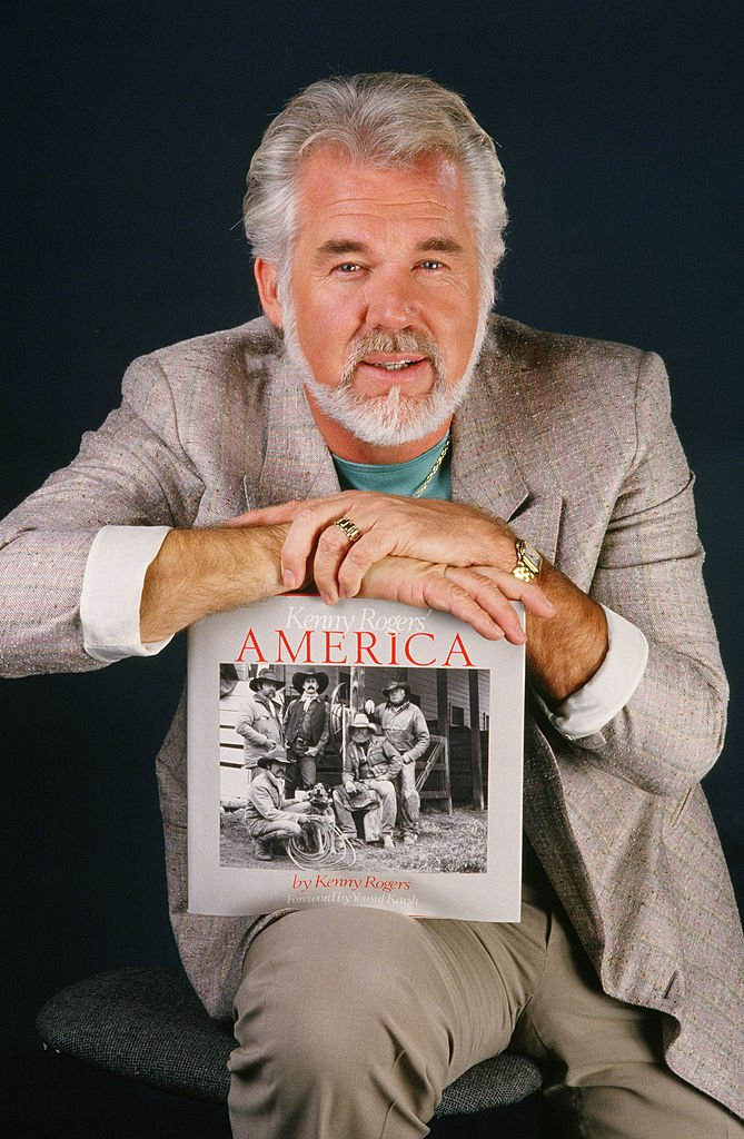 """Country music singer, actor and photographer, Kenny Rogers, poses during a 1986 Los Angeles, California, studio portrait session. Rogers was promoting his venture into photography and the release of his """"America"""" photo book.   Source: Getty Images"""