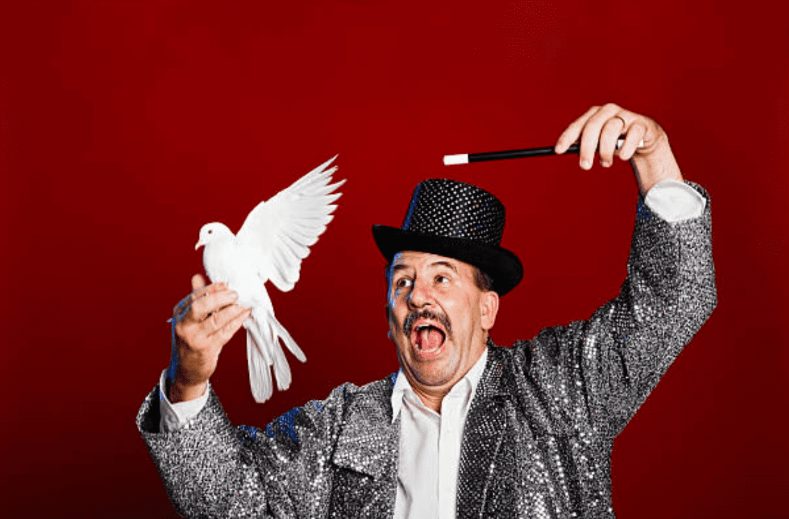 Magician holding a white dove and wand in his hand   Source: Getty Images