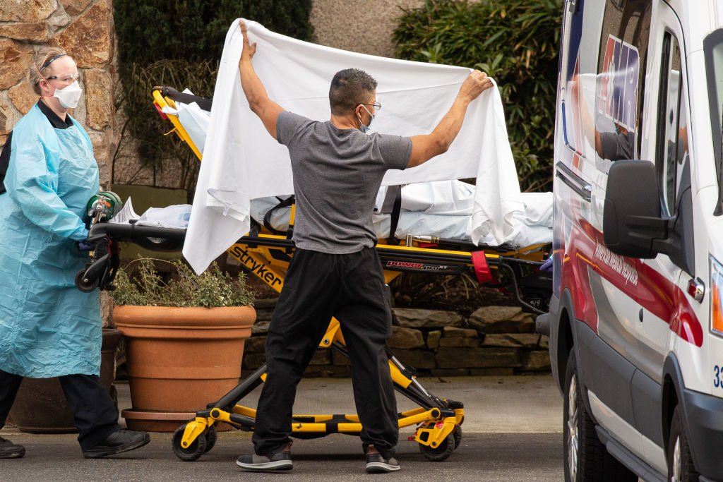 Healthcare workers transport a patient on a stretcher into an ambulance on February 29, 2020 in Kirkland, Washington. | Photo:Getty Images