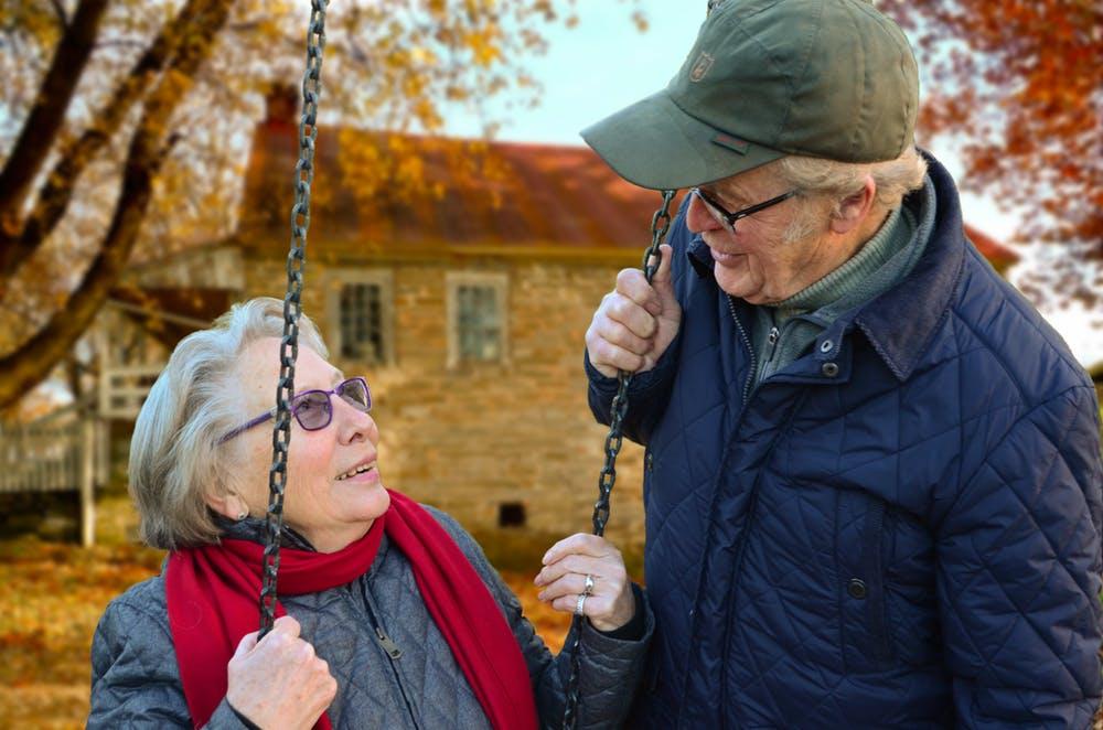 Un homme âgé se connectant avec sa femme assise sur une balançoire. | Pexels