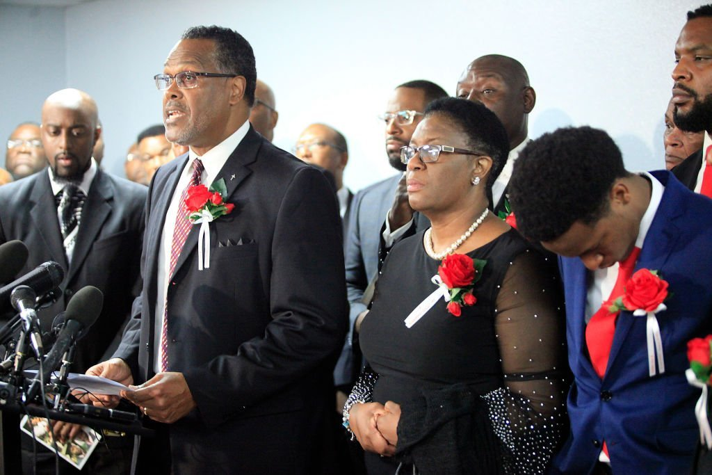 Sammie L. Berry speaks as church members stand with the family of Botham Shem Jean at Greenville Avenue Church of Christ after the funeral service | Photo: Getty Images