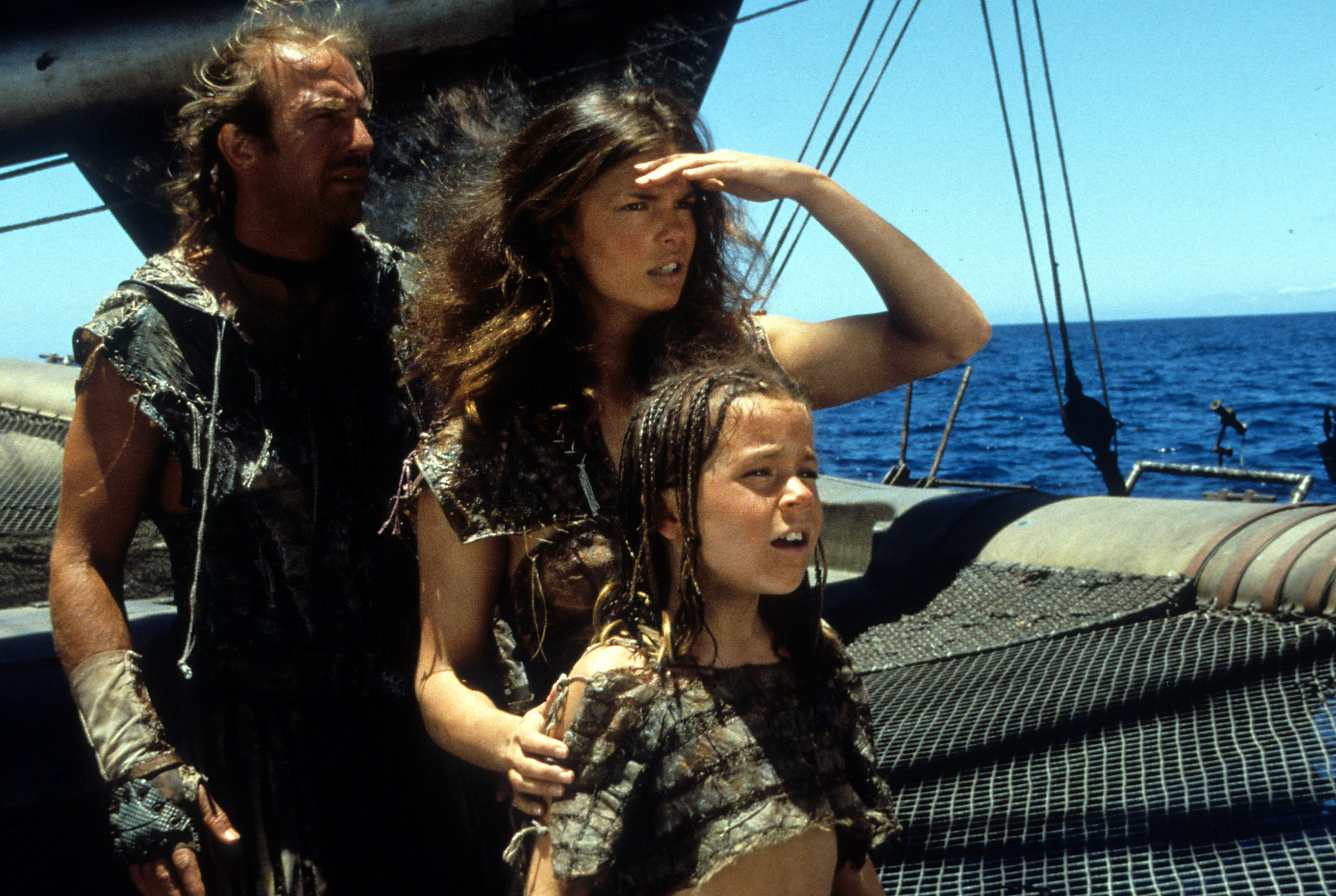 Kevin Costner, Jeanne Tripplehorn and Tina Majorino look to the horizon in a scene from the film 'Waterworld', 1995. | Source: Getty Images