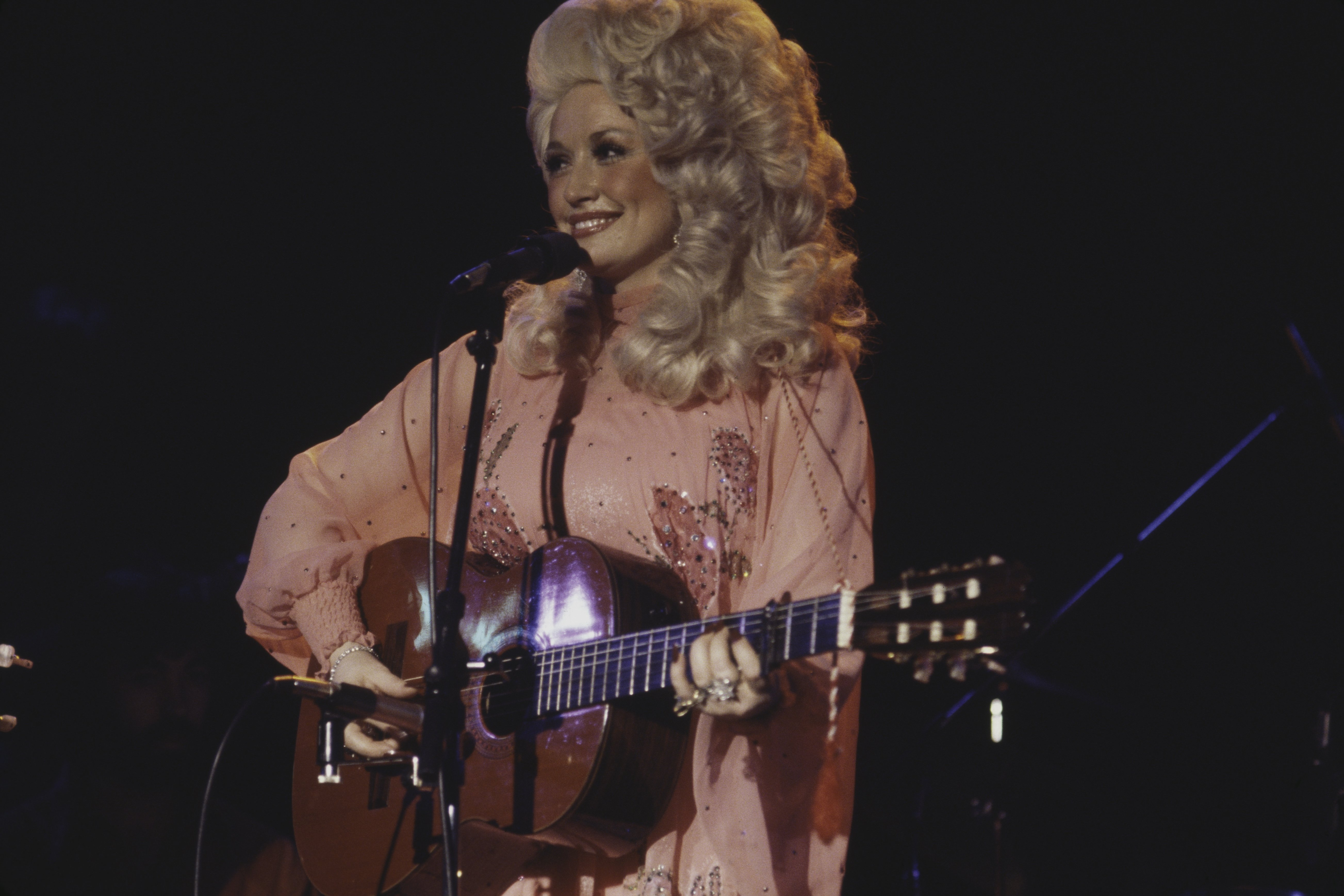 Dolly Parton performs live on stage at the Bottom Line club in New York on 11th May 1977. | Photo: GettyImages