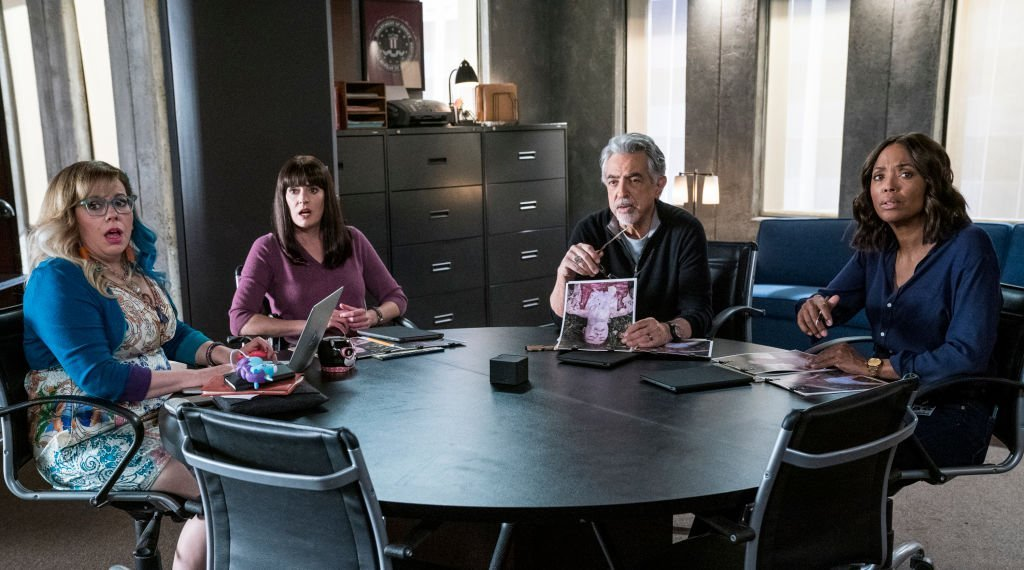 """Kirsten Vangsness, Paget Brewster, Joe Mantegna, and Aisha Tyler sit around a table for an episode of """"Criminal Minds"""" titled """"Under the Skin,"""" which aired on CBS January 25, 2019 
