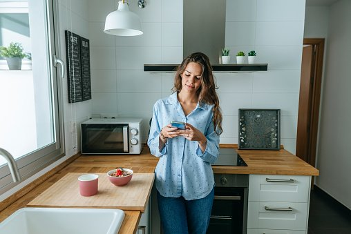 Photo of a young woman wearing pyjama in kitchen at home using cell phone | Photo: Getty Images