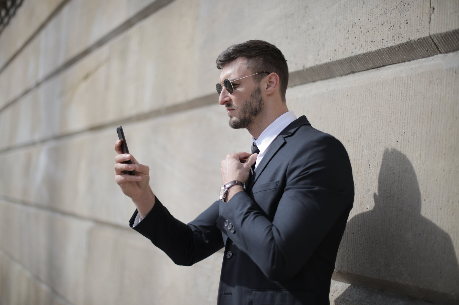 Man in a suit with his phone   Source: Pexels