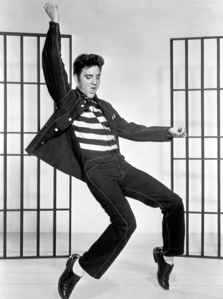 """Elvis Presley dancing in a stylized prison uniform in a promotional portrait for director Richard Thorpe's film, """"Jailhouse Rock""""   Photo: Getty Images"""