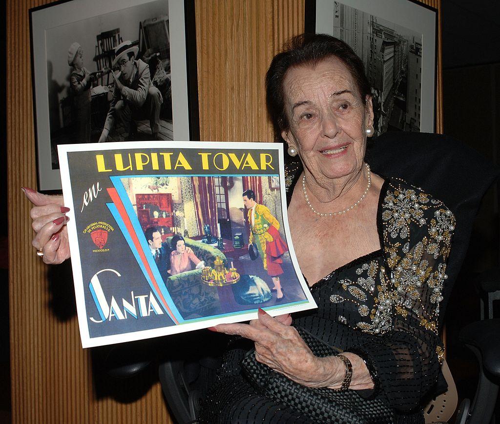 Lupita Tovar sostiene un póster de una de sus películas en su tributo en la Academia de Artes y Ciencias Cinematográficas el 7 de diciembre de 2006 en Beverly Hills, California. | Imagen: Getty Images