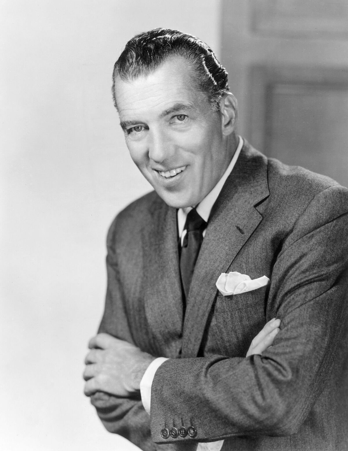Promotional portrait of American television variety show host, Ed Sullivan smiling with his arms crossed | Source: Getty Images