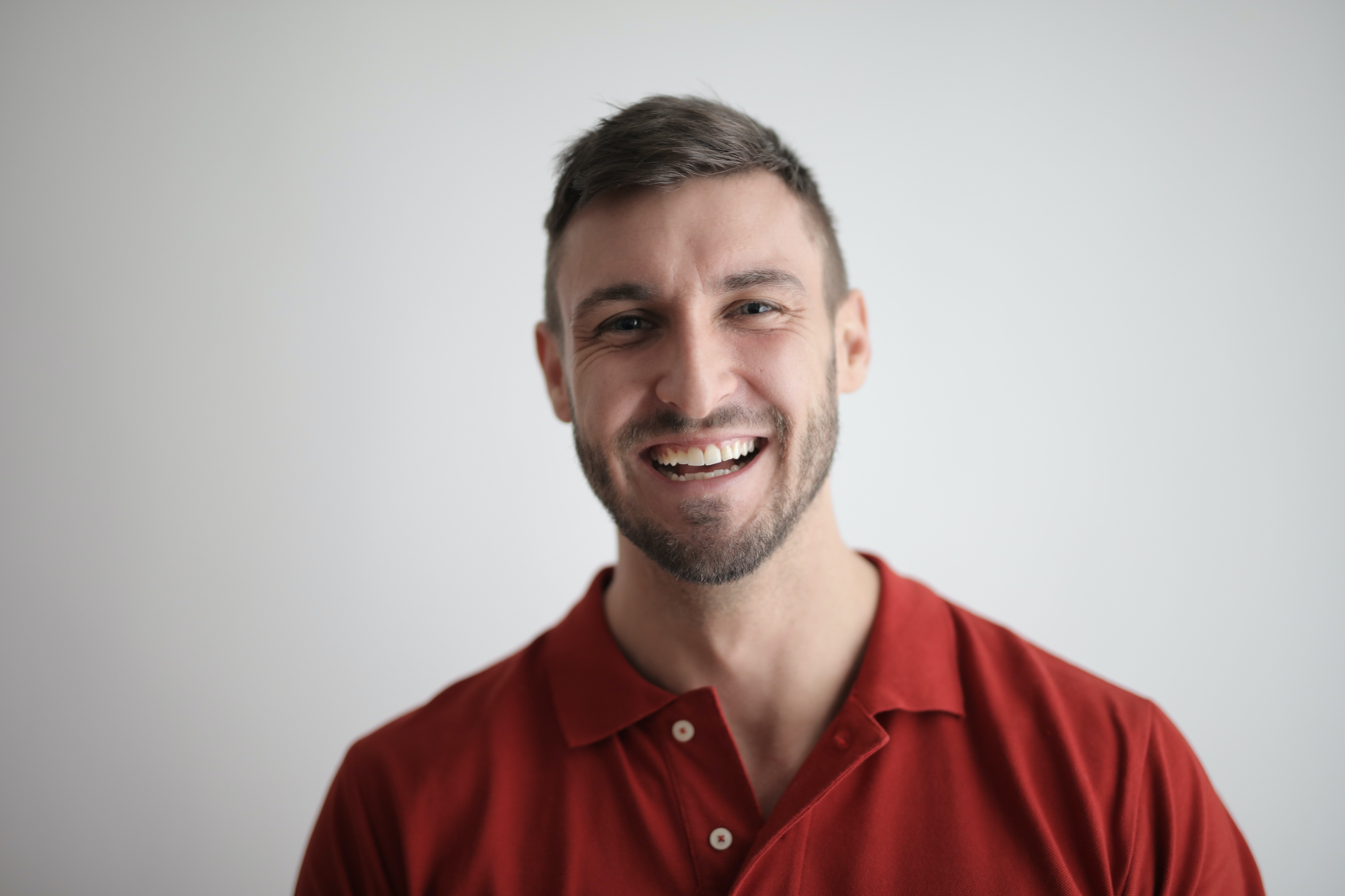 Man in a red button-up shirt smiling   Photo: Pexels