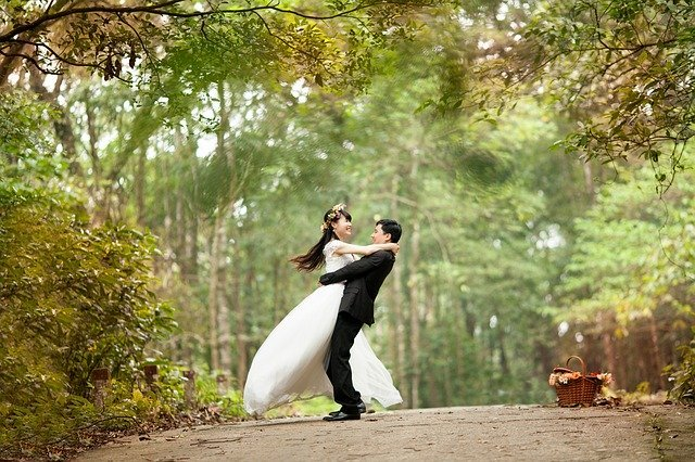 A groom lifts his bride up near some woods | Photo: Pixabay