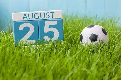 25 de agosto marcado en un calendario de madera junto a un balón de fútbol. | Fuente: Shutterstock